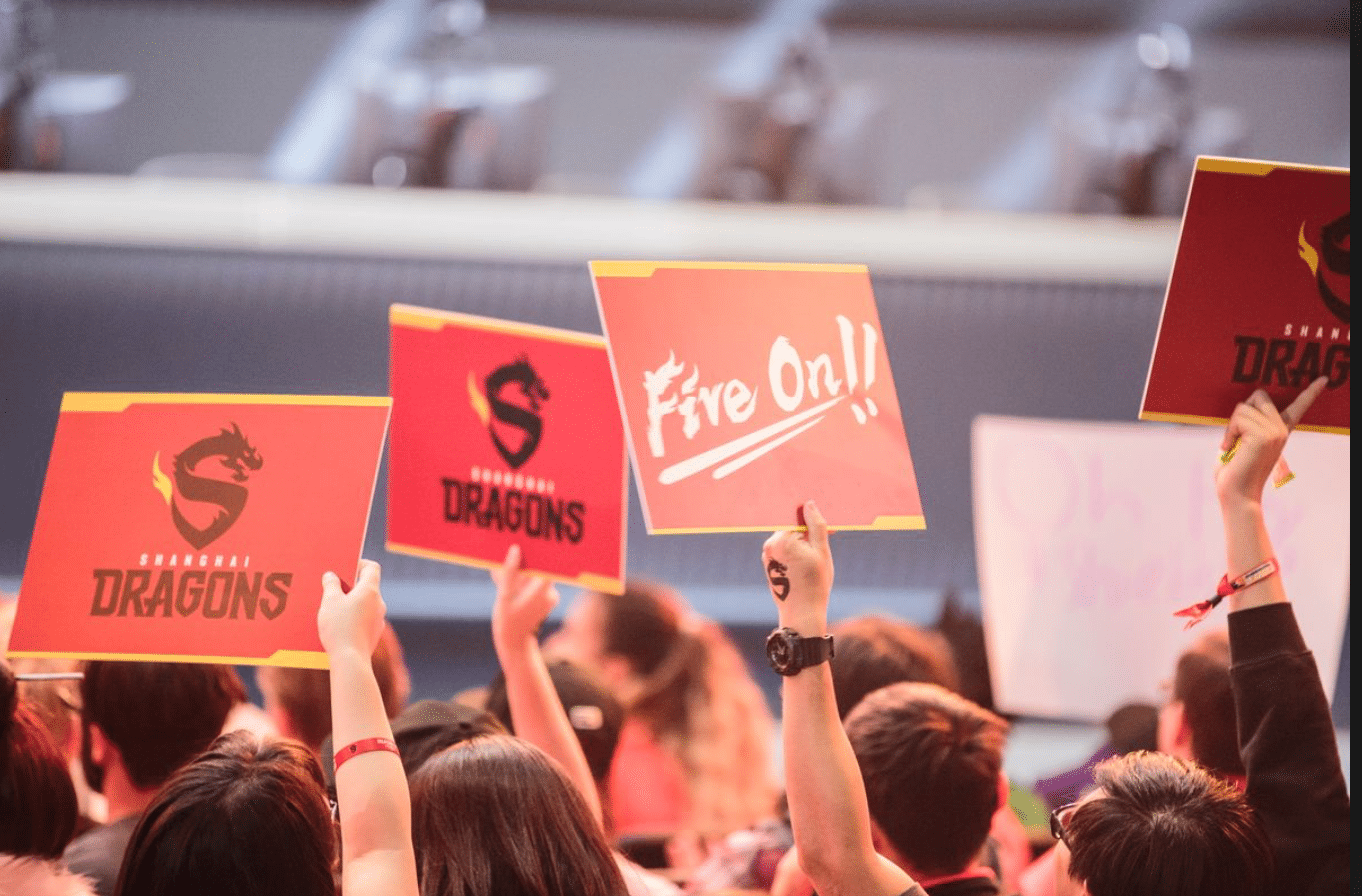 """The camera is positioned behind and slightly above the heads of a cheering crowd, who are holding up red signs displaying the Shanghai Dragons logo and the slogan """"Fire On!!"""""""